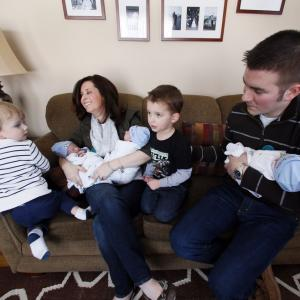 Family Celebrating One-Month Birthdays of Identical Triplets